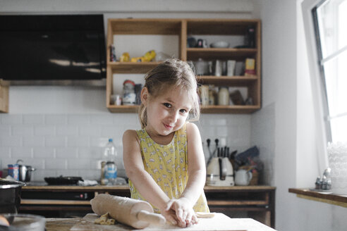 Portrait of smiling little girl kneading dough in the kitchen - KMKF00908