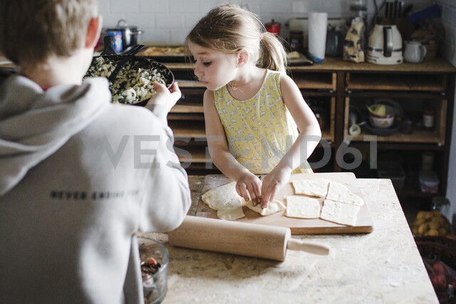 Little girl and her older brother preparing stuffed pastry in the kitchen - KMKF00911 - Katharina Mikhrin/Westend61