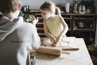 Little girl and her older brother preparing stuffed pastry in the kitchen - KMKF00911
