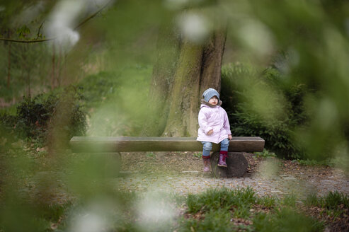 Little girl wearing blue hat and pink coat sitting on bench in a park - EYAF00189