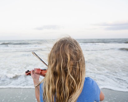 Rear view of Caucasian girl playing violin at beach - BLEF02073