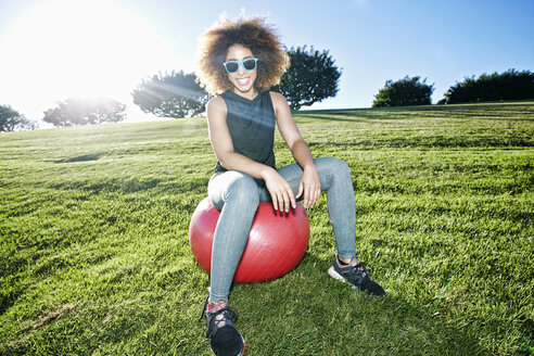 Portrait of smiling Hispanic woman sitting on fitness ball in field - BLEF02109