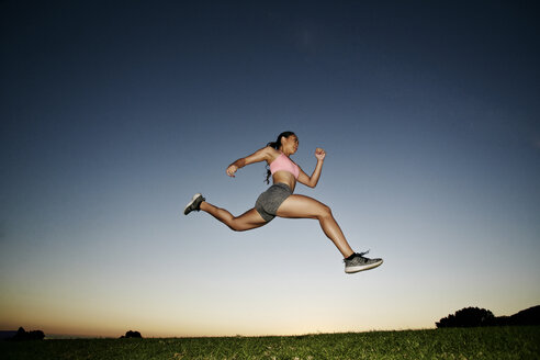 Mixed Race woman running and jumping in field at sunset - BLEF02112