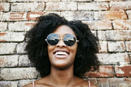 Laughing Black woman leaning on brick wall - BLEF02118