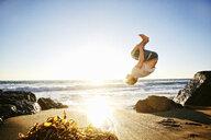 Caucasian man performing backflip on beach - BLEF02124