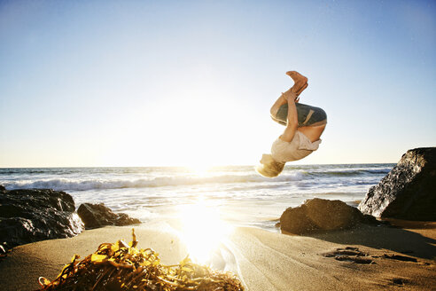 Caucasian man performing backflip on beach - BLEF02124