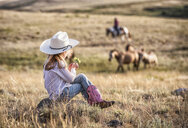 Caucasian girl sitting on rock in field holding flower - BLEF02145