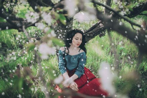 Petals falling from flowering tree on Caucasian woman - BLEF02265