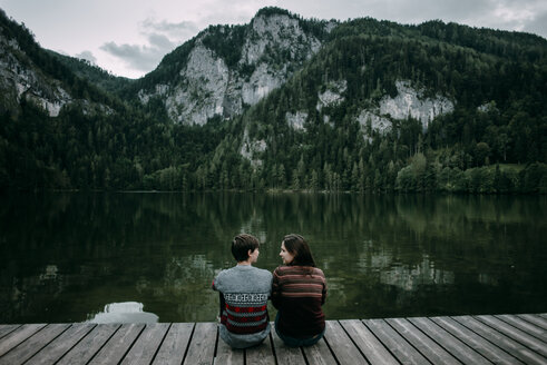 Caucasian couple sitting on dock near scenic view of mountain - BLEF02271