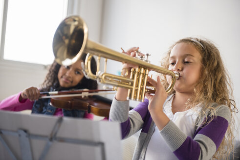 Girls practicing playing violin and trumpet - BLEF02302