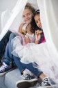 Girls wearing tutus in blanket fort on sofa - BLEF02305