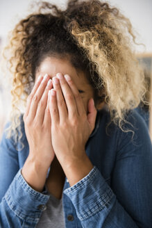 Mixed Race woman covering face with hands - BLEF02350