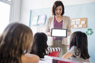 Teacher showing digital tablet to girls in classroom - BLEF02368