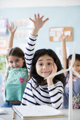 Girls learning about windmills raising hands in classroom - BLEF02380