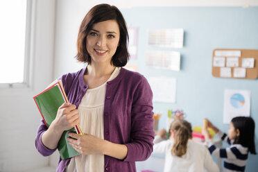 Portrait of smiling teacher holding notebooks in classroom - BLEF02389