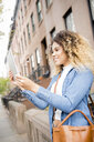 Mixed Race woman in city posing for selfie using digital tablet - BLEF02398