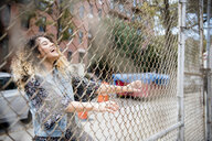 Laughing Mixed Race woman holding chain-link fence in city - BLEF02413