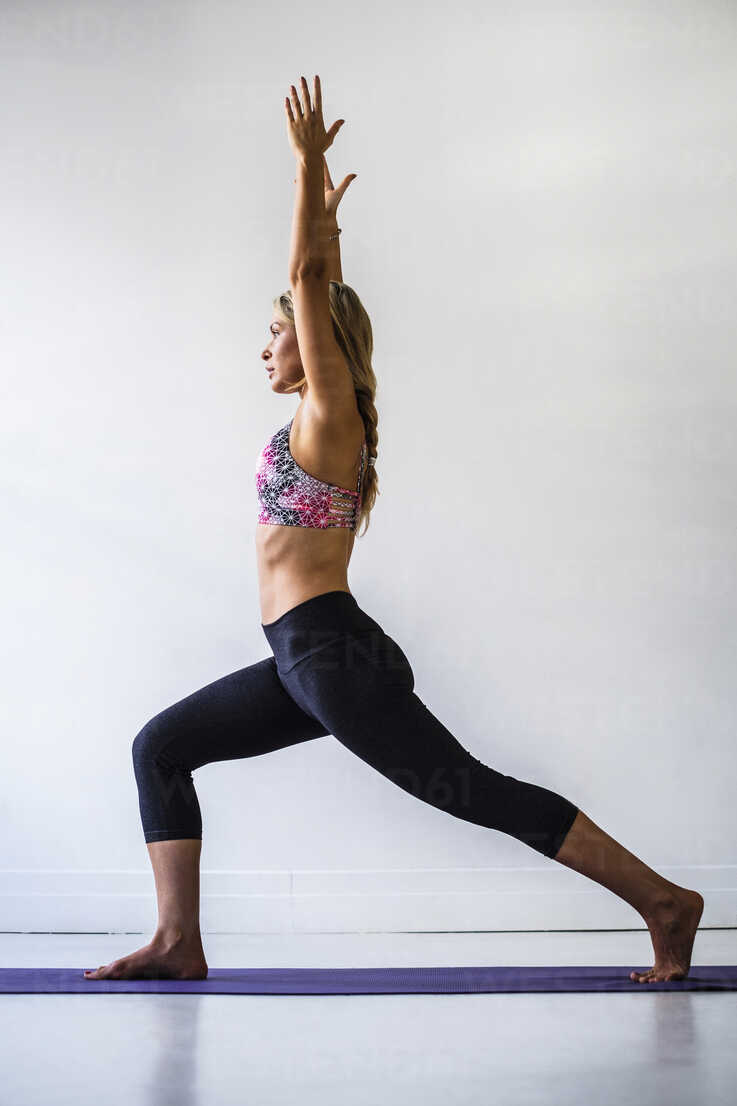Mixed Race Woman Stretching In Yoga Pose Stockphoto