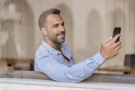Smiling businessman with cell phone behind windowpane - DIGF06935