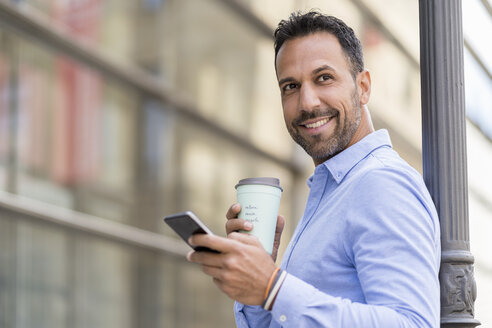 Smiling businessman with with takeaway coffee and cell phone in the city - DIGF06956