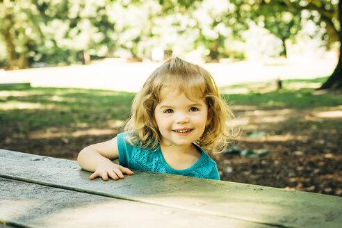 Portrait of Caucasian preschool girl at picnic table - BLEF02481