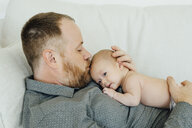 Father laying on sofa kissing baby daughter on head - BLEF02487