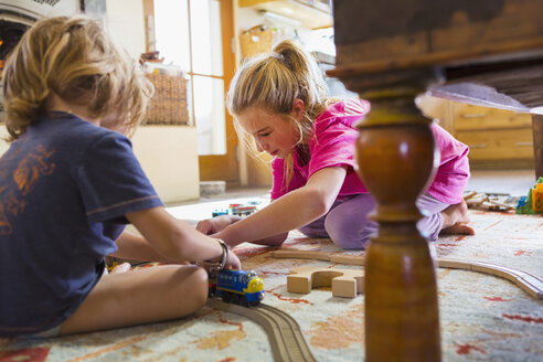 Caucasian brother and sister playing with toy race track on floor - BLEF02532