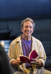 Portrait of smiling Caucasian actor holding script in theater - BLEF02538