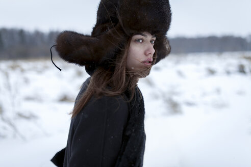 Serious Caucasian woman wearing fur hat and coat in winter - BLEF02607