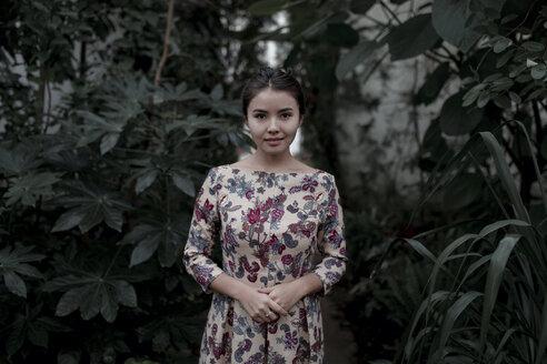 Asian woman smiling near foliage - BLEF02619