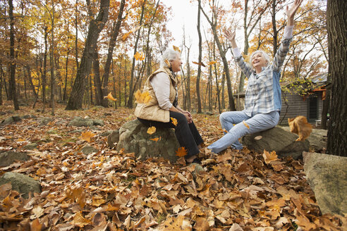 Caucasian women playing with autumn leaves - BLEF02709