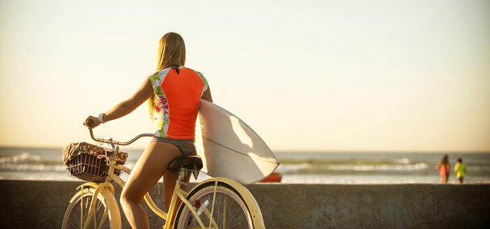 Caucasian teenage girl carrying surfboard on bicycle - BLEF02733