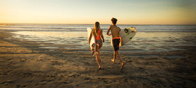 Teenage boy and girl carrying surfboards running to ocean - BLEF02748