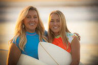 Portrait of smiling Caucasian mother and daughter holding surfboards - BLEF02751