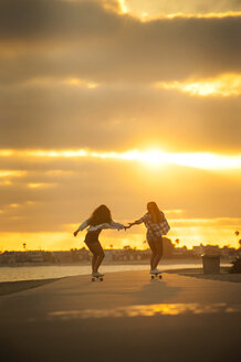 Girl holding hands while skateboarding on waterfront at sunset - BLEF02787
