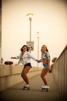 Teenage girls holding hands while riding skateboards - BLEF02793