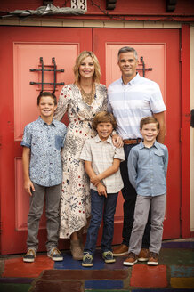 Portrait of smiling family posing near red doors - BLEF02799