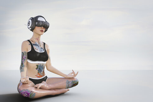 Woman with tattoos meditating and wearing virtual reality helmet - BLEF02829