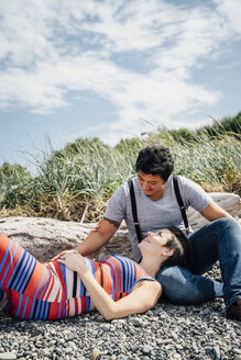 Pregnant lesbian couple relaxing on rocky beach - BLEF02847