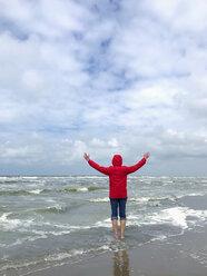 Belgium, Flanders, North Sea, woman standing barefoot in ocean waves, relaxing - GWF06072