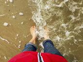 Belgium, Flanders, North Sea, woman standing barefoot on beach in ocean waves - GWF06075
