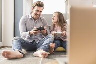 Young man and little girl playing computer game with gaming console - UUF17334