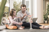 Young man and little girl playing with model of a wind turbine - UUF17361