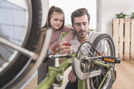 Young man and little girl repairing bicycle together - UUF17367