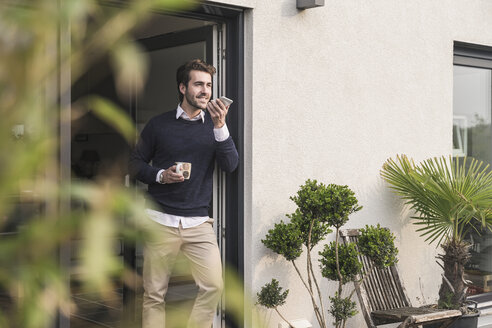 Young man leaning in door of his house, holding cup of coffee, using smartphone - UUF17376