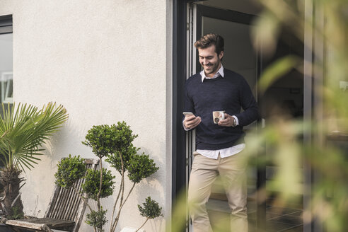 Young man leaning in door of his house, holding cup of coffee, using smartphone - UUF17379