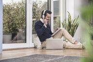 Young man sitting in living room, leaning on window, working with laptop, taking notes - UUF17382