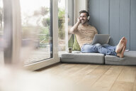 Young man sitting on mattress, using laptop with headphones - UUF17403