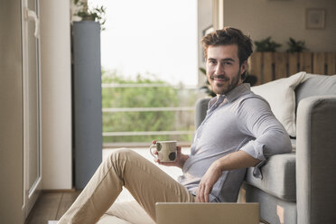 Young man sitting at home on floor, using laptop, drinking coffee - UUF17421