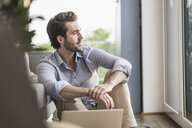 Young man sitting at home on floor, using laptop, looking out of window - UUF17430